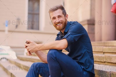 A man sits on a step and using a smartphone.