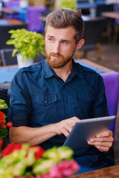 Redhead male using a tablet PC at the table.