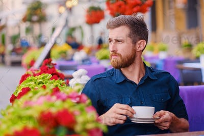 A man drinks coffee in a cafe on a street.