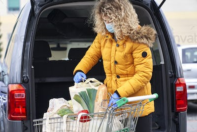 Woman finishing shopping and packing bags in the car trunk