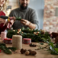 Table full of Christmas decorations and couple making Christmas wreath