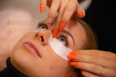 Close-up of eyelash extension procedure with clinic master and a client in a beauty salon