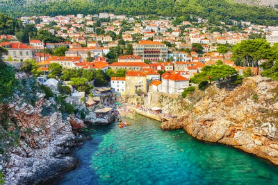 view at famous travel destination city of Dubrovnik -  Suluci beach and old  city on a sunny day.