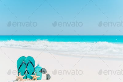 Suncream bottles, goggles, starfish and sunglasses on white sand beach background ocean