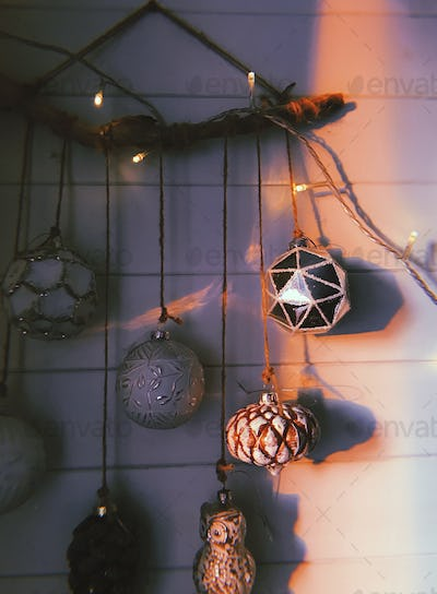 Christmas vintage baubles hanging on white wall. Aesthetic christmas decor, festive ornaments