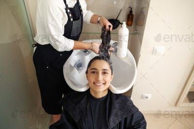 Hairdresser washes woman's hair, side view