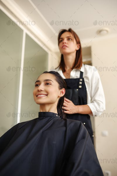 Hairdresser applies mousse on woman's hair