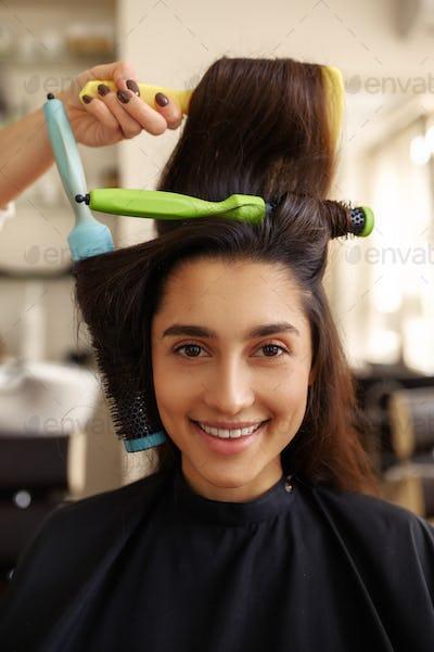 Hairdresser curls woman's hair, closeup view