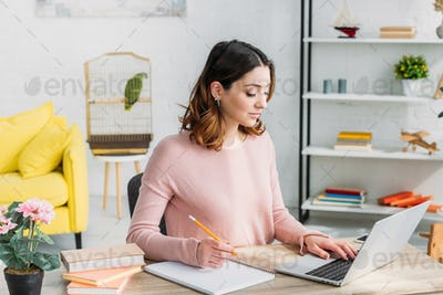 beautiful attentive woman working at home while sitting at home with laptop