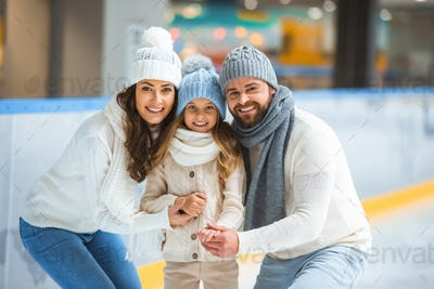 portrait of cheerful parents and daughter in sweaters looking at camera on skating rink