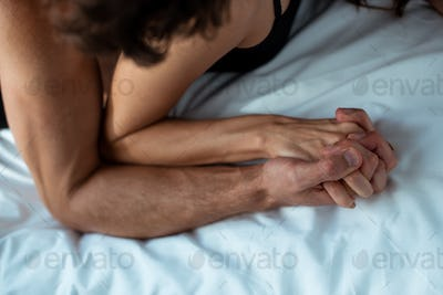 cropped view of passionate man and woman holding hands in bedroom