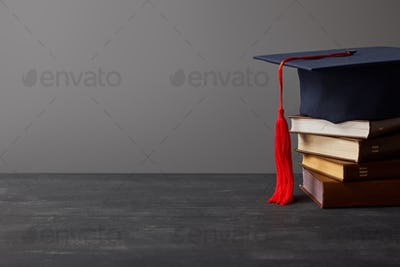 Brown books and academic cap with red tassel isolated on grey