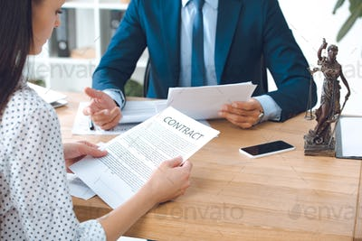 cropped shot of lawyer holding papers and client reading contract in office