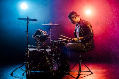side view of male musician in leather jacket playing drums during rock concert on stage with smoke