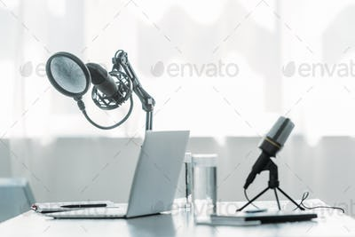 microphones, laptop and glasses with water on table in broadcasting studio