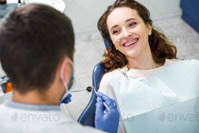 selective focus of cheerful woman in braces during examination of teeth near dentist