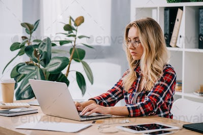 focused businesswoman using laptop while taking part in webinar
