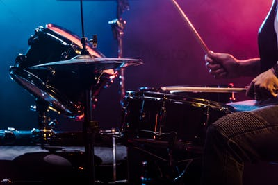 cropped shot of male musician performing on drums during rock concert on stage