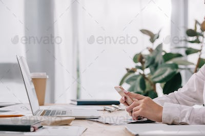 partial view of businesswoman with smartphone at workplace with documents and laptop in office