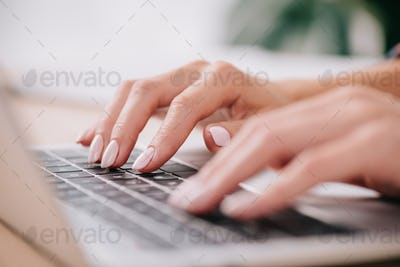 partial view of eoman typing on laptop