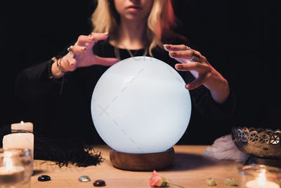 cropped view of female esoteric holding hands above magical crystal ball isolated on black