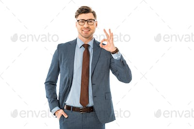 smiling businessman in glasses and suit showing ok sign isolated on white
