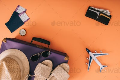 top view of summer accessories on travel bag, plane model, wallet and passports with tickets on