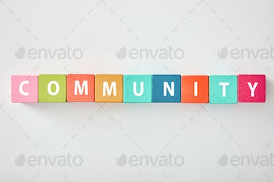 top view of community lettering made of multicolored cubes on grey background