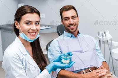 selective focus of attractive dentist in latex gloves holding teeth model near patient with clenched