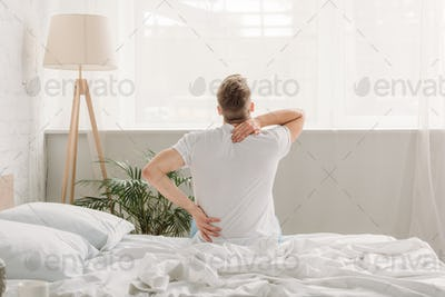 back view of man sitting on white bedding and suffering from back pain