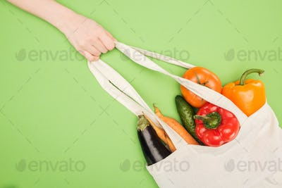 partial view of woman holding handle of cotton bag full of ripe vegetables