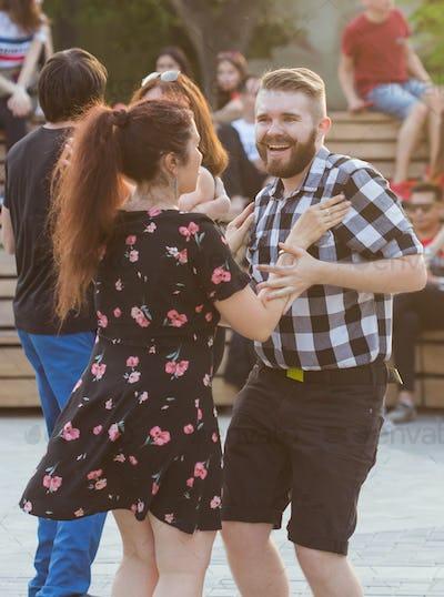 Kizomba, bachata or salsa concept - beauty couple dancing social dance on open air party