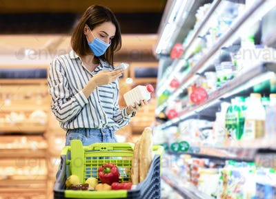 Woman in mask scanning code on products using smartphone