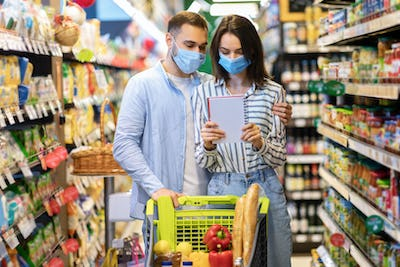 Couple Wearing Face Masks In Hypermarket, Checking Shopping List