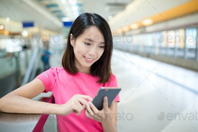 Asian Woman use of mobile phone in train platform