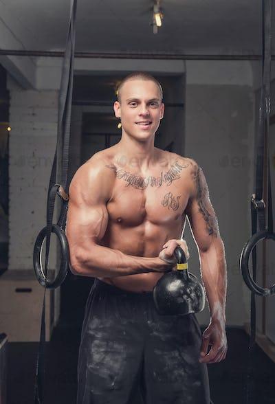 Tattooed shirtless man holds lifting weight.