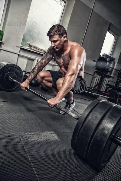Tattooed muscular man standing on knees.