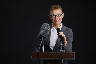 Mature Woman Speaking to Microphone at Podium