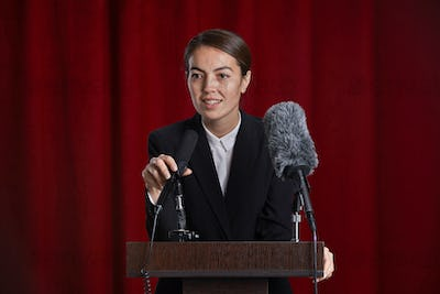 Young Woman Giving Speech on Stage