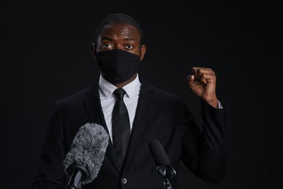 African Man Speaking to Microphone Wearing Mask