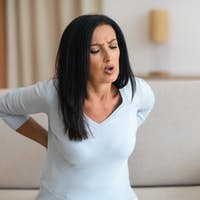 Mature lady having back pain while sitting on couch