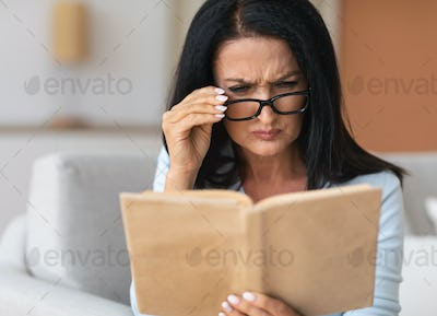Senior confused woman in glasses trying to read book