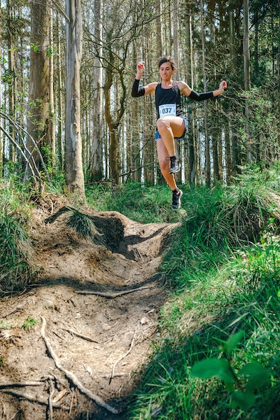 Woman jumping participating in trail race