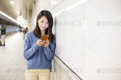 Woman use of smart phone in underground subway station
