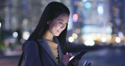 Woman looks at mobile phone in city at night
