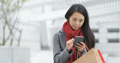 Woman use of smart phone and holding shopping bag