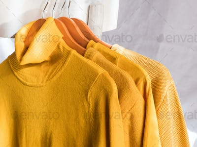 Yellow illuminated color winter sweaters on hangers