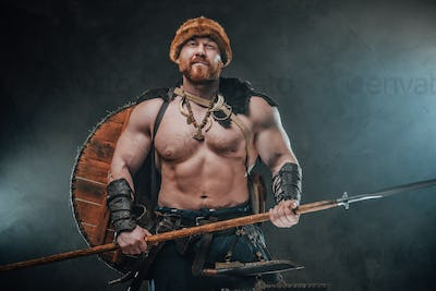 Smiley viking with hat and spear in dark and smokey background