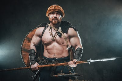 Shirtless viking armed with spear poses in smokey background