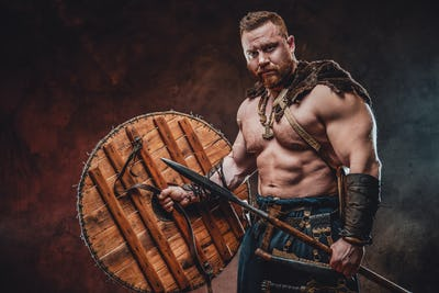 Brutal scandinavian barbarian with spear and shield in dark background